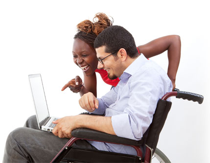Young woman with young man in a wheelchair, holding a laptop.